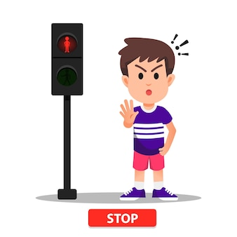 Boy with a pose of stopping according to the traffic light