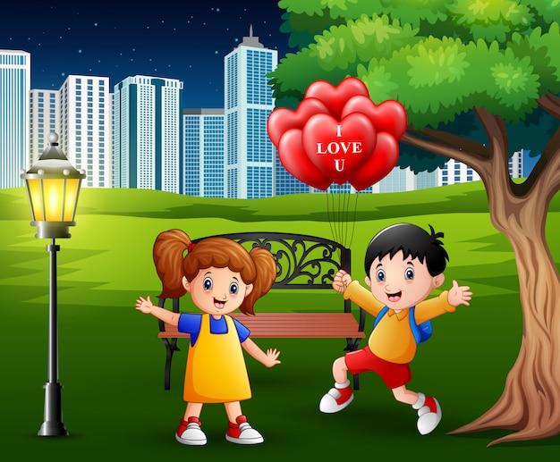 女の子に赤いハート型の気球を与える男の子