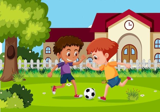 男の子は庭でサッカーをしています