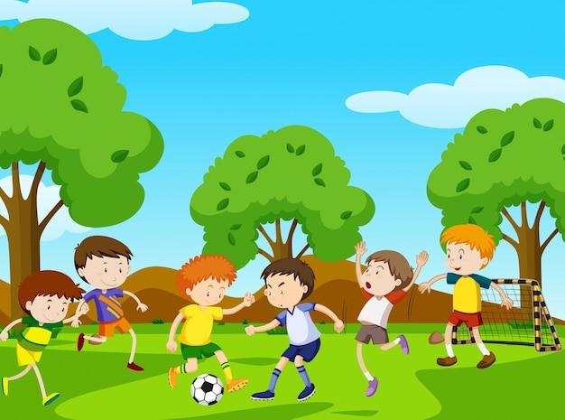 Мальчики играют в футбол в парке