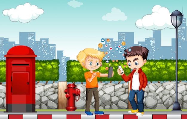 都市の背景にソーシャルメディアアイコンをテーマにしたスマートフォンを使用している男の子