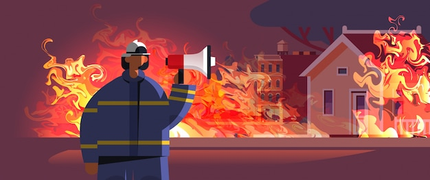 ユニフォームとヘルメットの消防緊急サービス消火コンセプト消火家の外観のオレンジ色の炎の肖像画でスピーカー消防士を保持している勇敢な消防士
