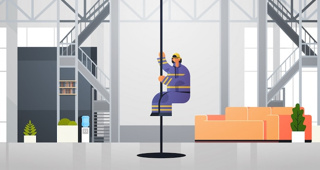 Brave fireman sliding down the pole firefighter wearing uniform and helmet firefighting emergency service concept modern fire department interior flat horizontal full length
