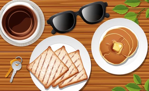 朝食はいくつかの葉の小道具とデスクの背景にクローズアップ