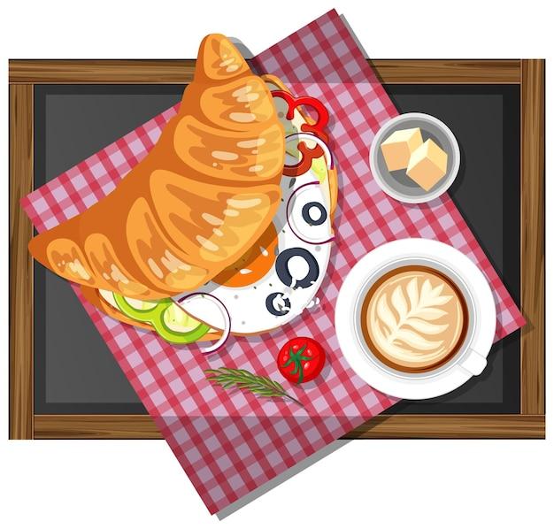 分離された木のプレート上のコーヒーのカップと朝食クロワッサンサンドイッチ