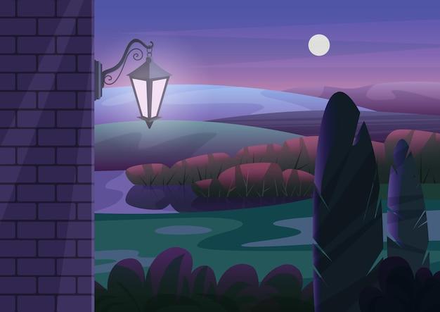 Кирпичная стена со светящимся фонарем на фоне садовых кустов и холмов в темную ночь