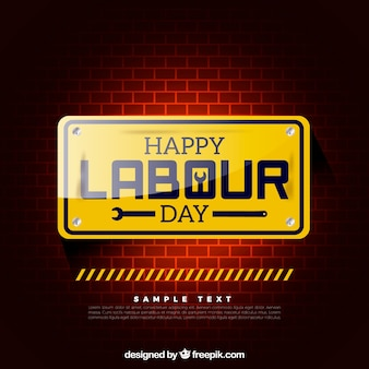 Brick wall with yellow sign for labour day