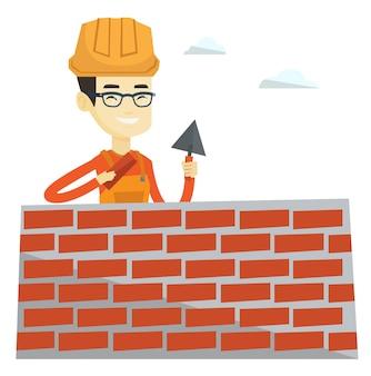 Каменщик работает шпателем и кирпичом.