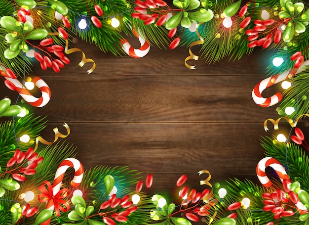 Bright christmas decorations with candies leaves and fairy lights on brown wooden background realistic