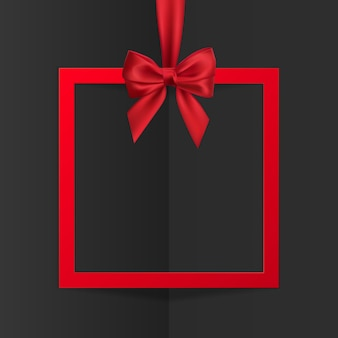 Bright holiday gift box frame banner hanging with red ribbon and silky bow on black background.