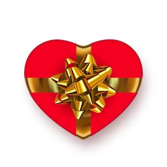 Яркая, красная подарочная коробка в форме сердца с блестящим золотым бантом