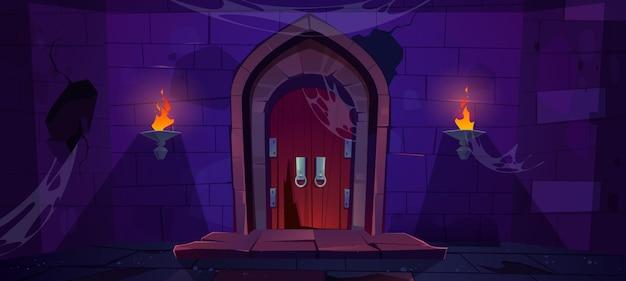Porta di legno rotta nel vecchio cancello di legno del castello medievale nel muro di pietra con torce fiammeggianti di notte