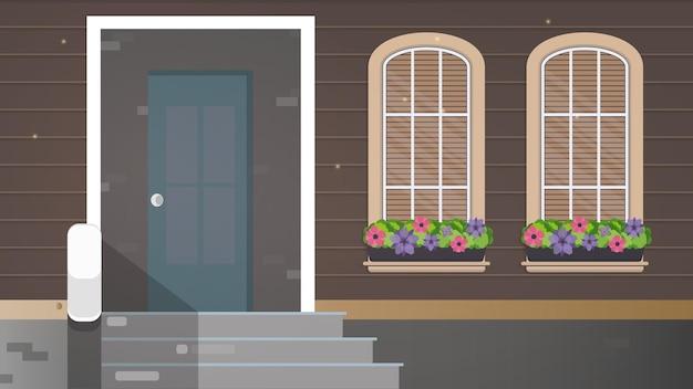 Коричневый деревянный дом с большими окнами. окна с цветами. крыльцо загородного дома.