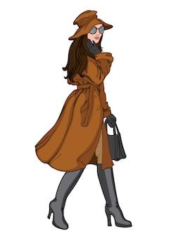 포즈를 취하는 그녀의 얼굴에 미소 가을 옷에 갈색 머리 여자. 갈색 모자, 코트, 바지, 검은 장갑, 선글라스, 핸드백 및 부츠