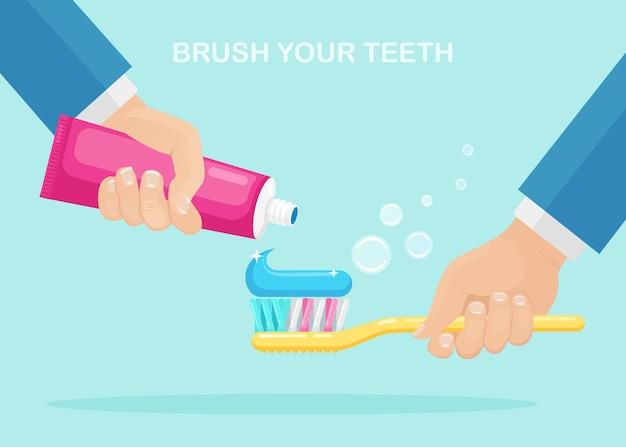 歯磨き。男は歯ブラシと歯磨き粉のチューブを保持します。デンタルケアのコンセプト。口腔衛生