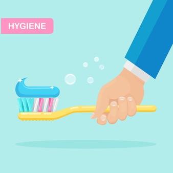 歯磨き。男は歯ブラシを保持します。デンタルケアのコンセプト。歯磨き粉の泡。口腔衛生