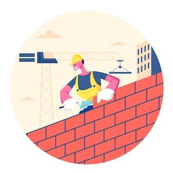 Строитель мужского пола в шлеме и униформе держит шпателем кладет бетон для кладки кирпичной стены и радуется работе