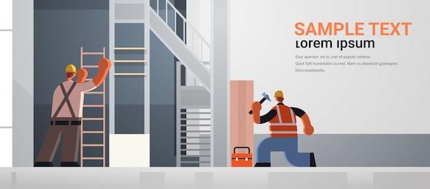 건축 개념 건설 현장 내부 후면보기 평면 전체 길이 가로 복사 공간 유니폼 작업 망치와 사다리 바쁜 노동자 팀을 사용하여 빌더 커플