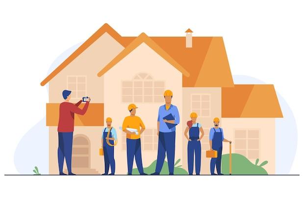 Команда строителей позирует для фото перед домом