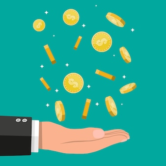 Buisnessman hand catching falling gold coins.