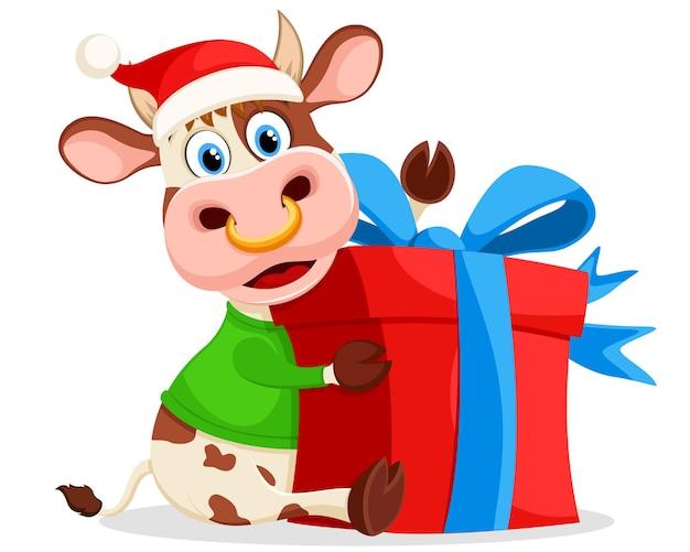 Бык с подарком в новогодней шапке и свитере на белом фоне. год быка