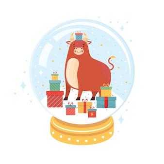 クリスマススノーボールの中に贈り物の山を持つ雄牛。面白い漫画の牛とクリスマスのガラス玉