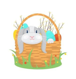Кролик сидит в корзине с пасхальными яйцами и ветками ивы