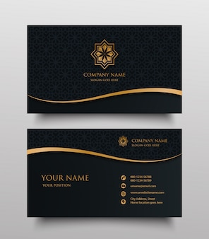 Business card with gold floral ornamental logo and place for text on dark background