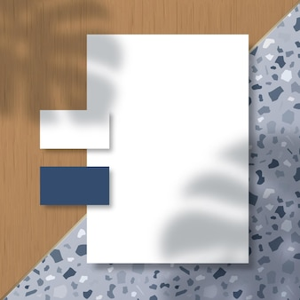 Monstera palm 잎 그림자 오버레이가있는 terrazzo 패턴 및 목재 타일 표면의 명함 및 레터 헤드