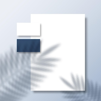 Business cards and letterhead on a surface surface with a tropical fern palm leaves shadow overlay