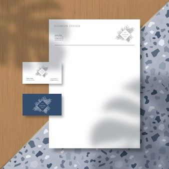 Business cards and letterhead on terrazzo pattern tile and wooden surface background with a monstera...