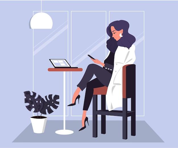 スマートフォンでカフェで働く上品なビジネス女性
