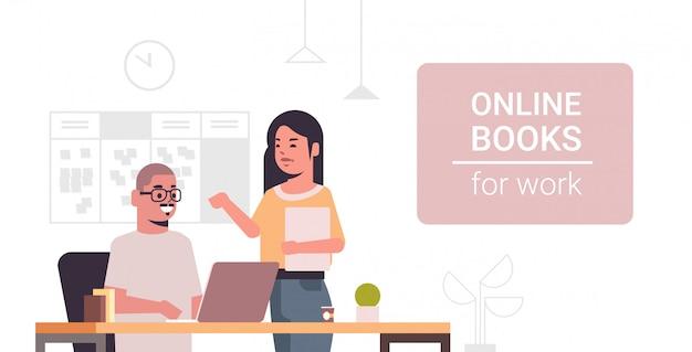 職場の現代オフィスインテリアのオンライン本を読んで職場のデスクのカップルでラップトップを使用してビジネス部門の同僚