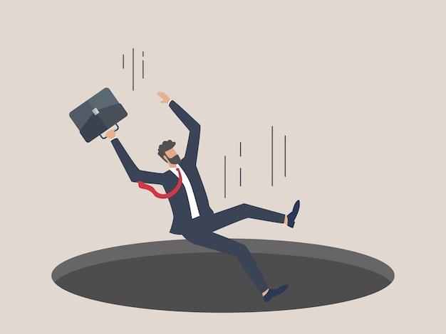 ビジネスマンが穴に落ちるビジネス危機と金融不況の概念