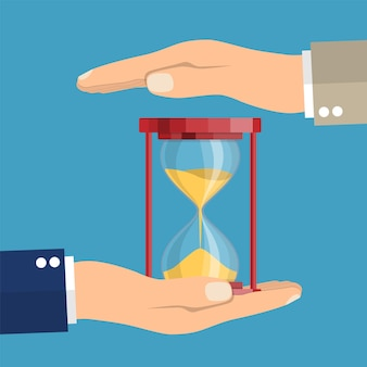 Business hand holding a hourglass