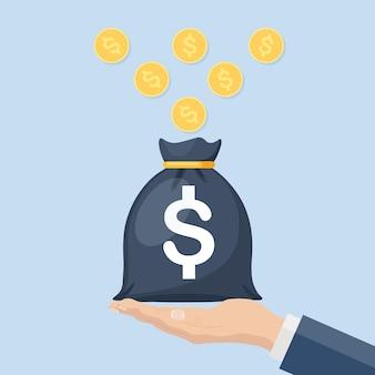 ビジネスマンは金貨でお金の袋を保持します。富、貯蓄、投資