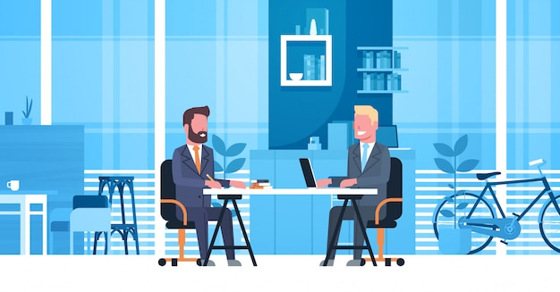 Business man on job interview with hr manager, two businessmen sitting at desk on meeting in creativ