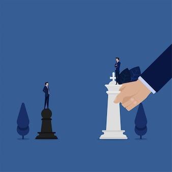 Бизнесмен стоя над пешками бросает вызов для метафоры короля шахмат стратегии.