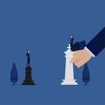 Business man standing above pawns challenge for king chess metaphor of strategy.