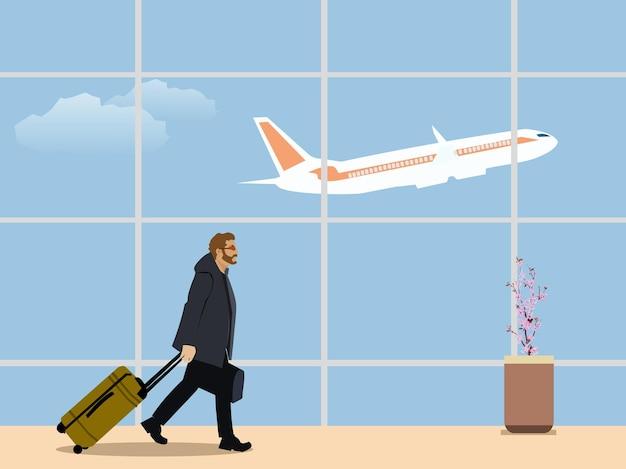 飛行機に乗るために空港で車輪付きの荷物を持って歩いているビジネスマン。飛行機と空を背景に。