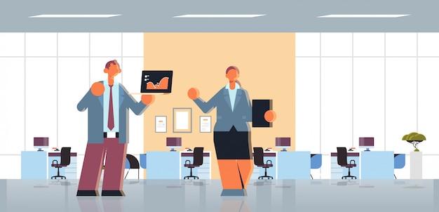 ビジネス男性女性カップルプレゼンテーションモダンなオフィスインテリアフラット全長水平を作るラップトップとクリップボードの財務図統計データレポート同僚を提示