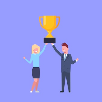 Business man and woman holding together golden cup successful businessman and businesswoman team winners