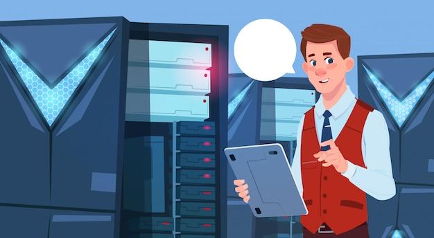 Деловой человек, работающий на цифровом планшете в современном центре данных или серверной комнате бизнесмен инженер