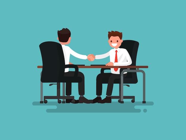 ビジネスパートナー。デスクの図の背後にある2人のビジネスマンの握手