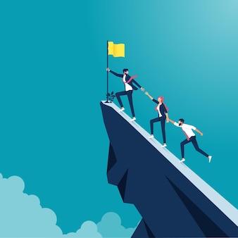 Деловые люди поднимаются на вершину горы, лидер помогает команде подняться на скалу