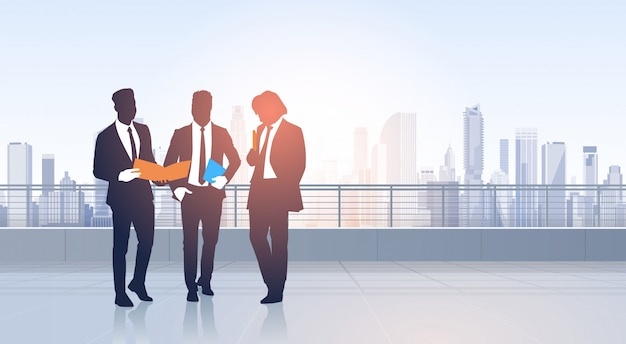 Business people group meeting silhouettes over city landscape modern office buildings