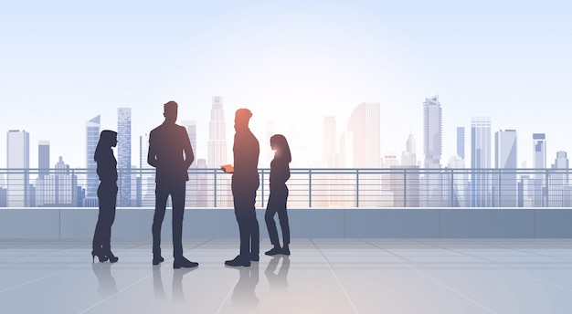 Business people group silhouettes over city landscape modern office buildings