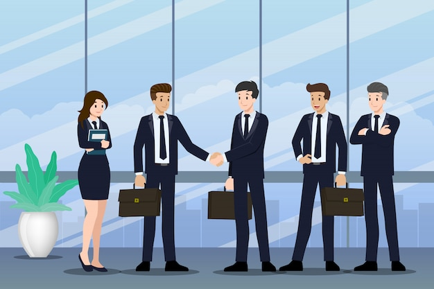 Деловые люди стоят и пожимают друг другу руки.