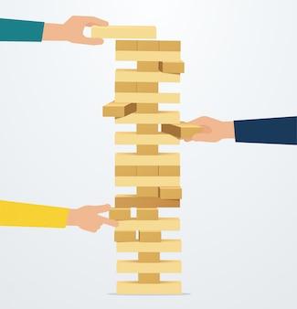Бизнес-стратегия и риск. руки кладут деревянные блоки на башню. командное мышление, мозговой штурм