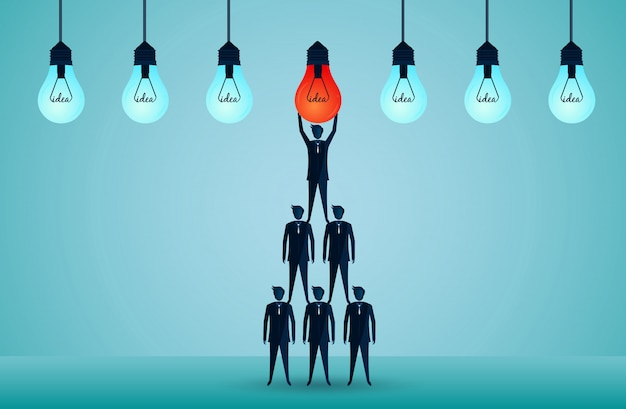 Business teamwork concept. businessmen standing on each other lifting the red light bulb upwards. harmonious. creative idea